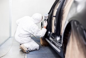 worker painting a car in a special painting box